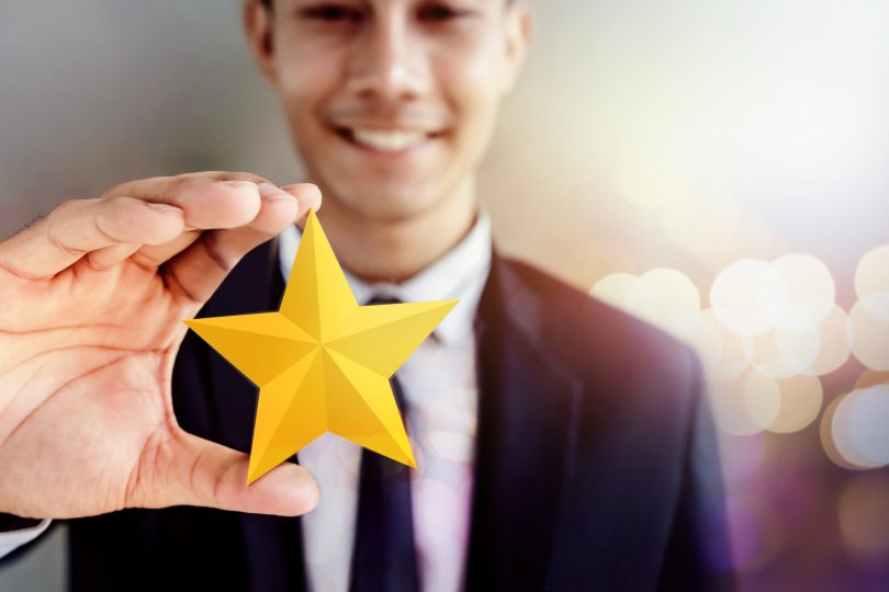 Success in Business or Personal Talent Concept. Happy Businessman in black suit Smiling and Showing a Golden Star in Hand