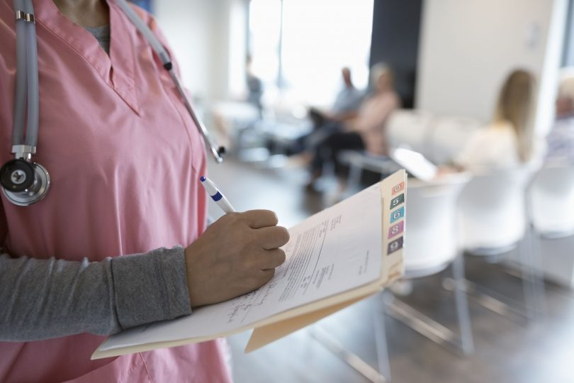 close up female nurse writing on medical record in clinic waiting room 1015130176 8342f028c4db46eca51788346e70185f