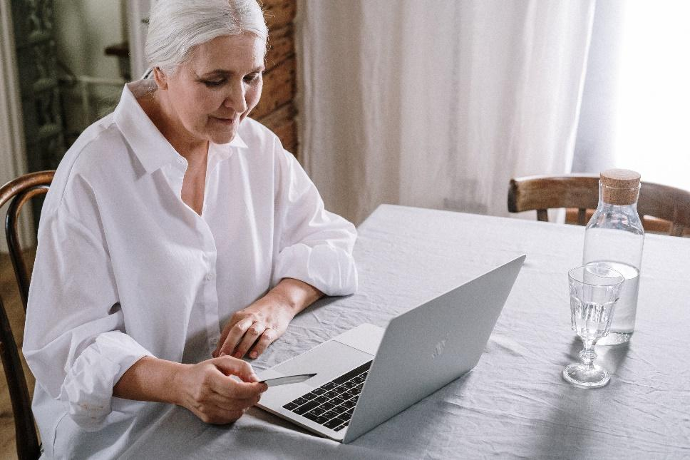 A person sitting at a table using a computer Description automatically generated
