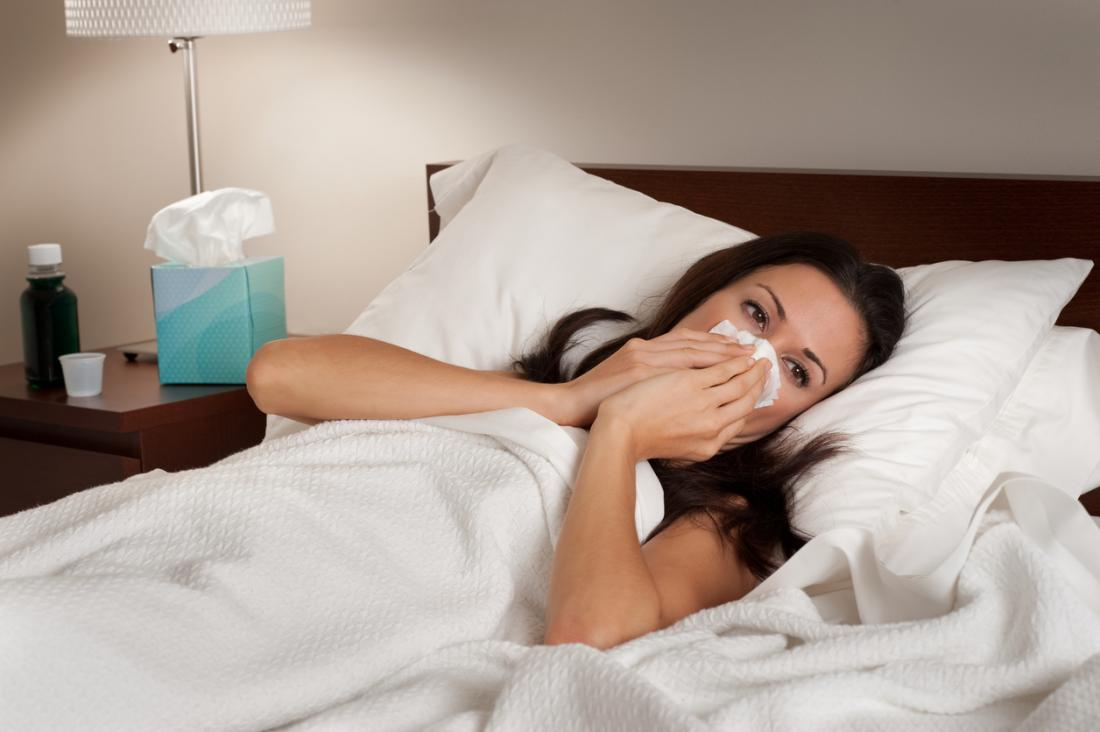 woman-with-cold-laying-in-bed-blowing-her-nose