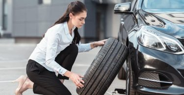 Woman relplacing tire on car