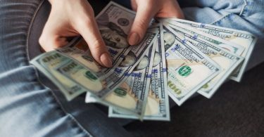 Person Holding 100 Us Dollar Banknotes