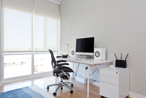 It's not exactly news that office jobs aren't good for us. This is something we've known now for a long time and more and more evidence is only supporting this view. Perhaps most damning are the recent studies on the negative effects of sitting at work. These show us that sitting for long stretches at a desk can take years off our life, and undo all the good work we've put in at the gym. The problem is that most people don't have much choice – they work in an office to make a living and as such they don't get to make the rules regarding how long they're sitting. That's where creating a home officemakes all the difference. If you're fortunate enough to be able to work from home at least some or all ofthe time, then you can make the rules yourself. Here are some of the things you can do to design that office to promote better health. Standing Desk One of the first things you can use to improve your health when you're working in the office is to invest in a standing desk. Now you're not going to want to use this all the time, as it's hard to concentrate and get real work done when you're standing up. Nevertheless, for short bursts while you check e-mails etc., standing up could be a very useful way to feel healthier and even to burn some calories. Multiple Seats One of the things that makes working in an office so bad is simply how long we're remaining in the same position for. The position isn't great, but staying in any pose for this duration would be bad for you. So, a solution to this issue is to work on a laptop or a 'hybrid slate' computer, and to then have multiple seats around the office that you can move to. One of these seats could be a 'kneeling chair'. These encourage you to take up a somewhat kneeling position, which while still not perfect will at least straighten out your back allowing you to breathe more naturally and reducing the shortness of your hip flexors (which is one of the things that contributes to lower back pain). The Desk Of course, your reg